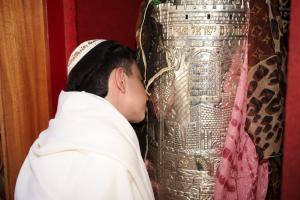 мальчик целует свиток торы во время молитв бар мицва